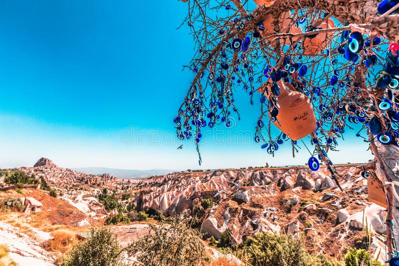 Evil Eye Beads on Tree and Fairy tale chimneys in Guvercinlik Valley. Branches of old tree decorated with the eye-shaped amulets,Nazars,Evil eye royalty free stock photo