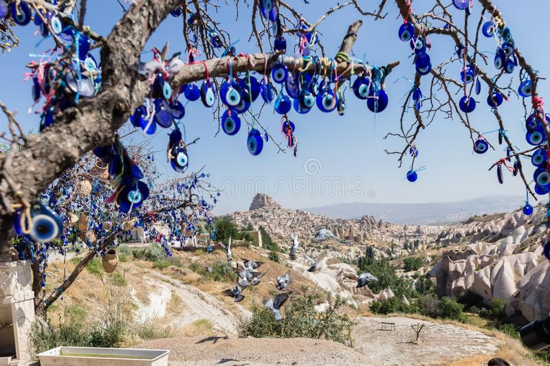 Evil Eye Beads on Tree and Fairy tale chimneys in Guvercinlik Valley. Branches of old tree decorated with the eye-shaped amulets,Nazars,Evil eye stock photo