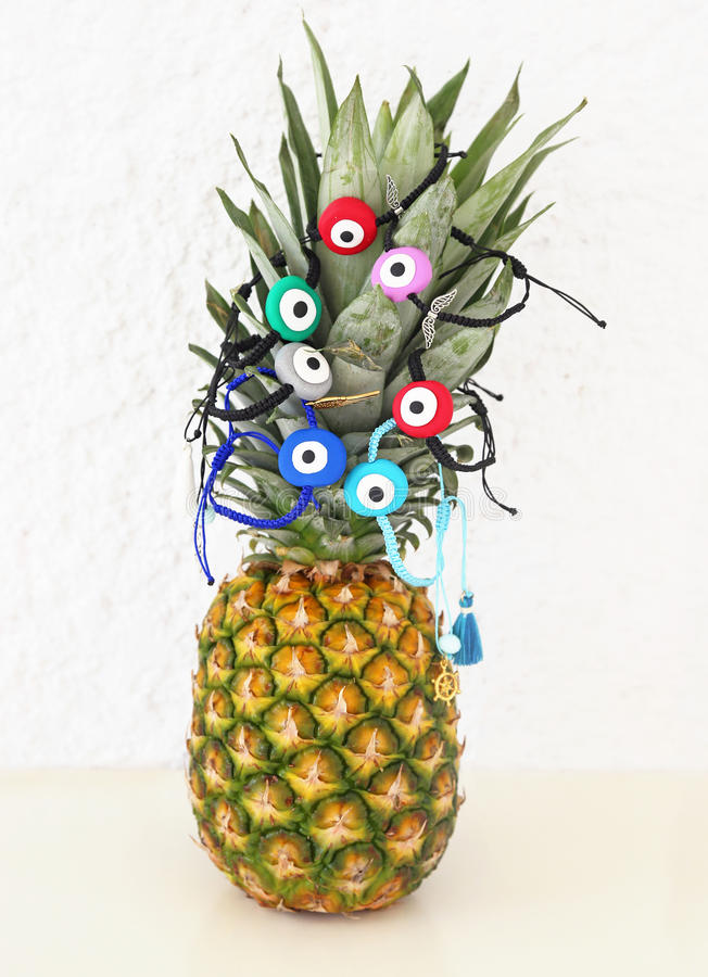 Evil eye bracelets advertisement on pineapple. Exotic fruit with greek jewelry royalty free stock photography