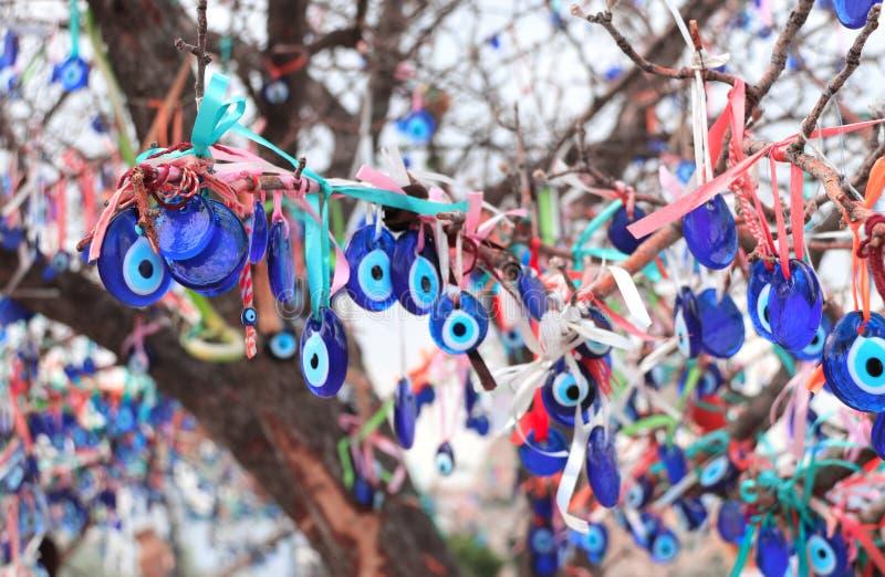 Evil eye charms hang from a tree in Cappadocia, Anatolia, Turkey. Many glass mascots - evil eye charms hang from a tree in Cappadocia, Pigeon valley, Turkey royalty free stock photos