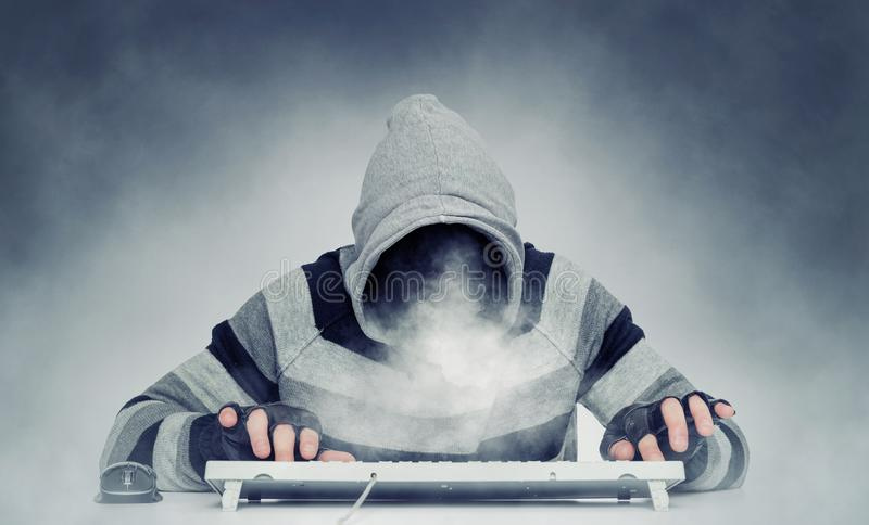 Evil hacker man anonymous in hoodie behind the keyboard, smoke instead of face. royalty free stock images