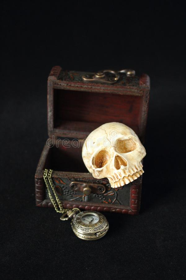 An evil human skull with a pocket watch on a pirate treasure chest on a black background. Evil human skull with a pocket watch on a pirate treasure chest on a stock photography