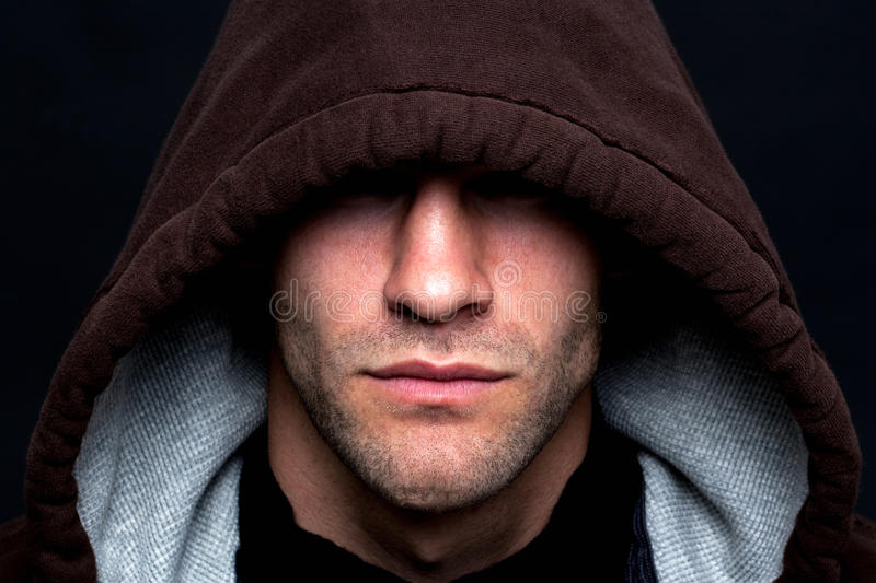 Evil looking hooded man royalty free stock photos