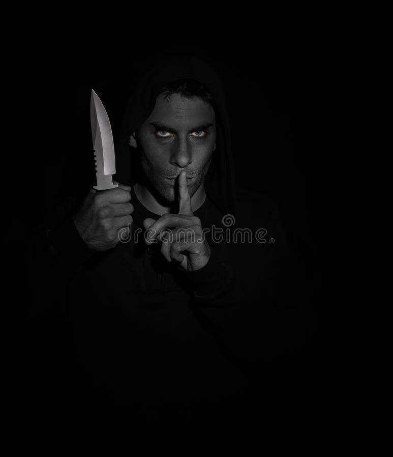 Evil man gesturing silence while holding a knife royalty free stock photos
