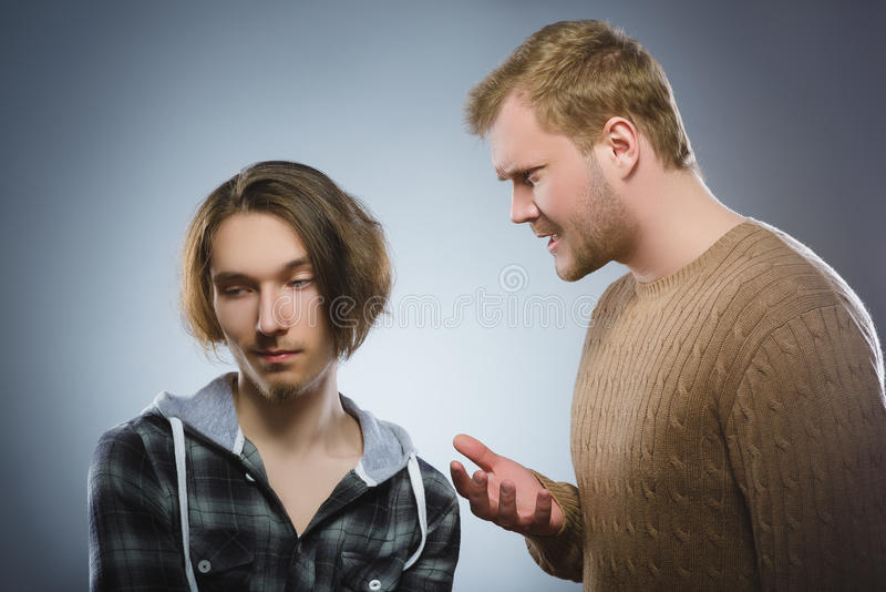 Evil man yelling at the teenager. The elder brother scolds the younger royalty free stock photos