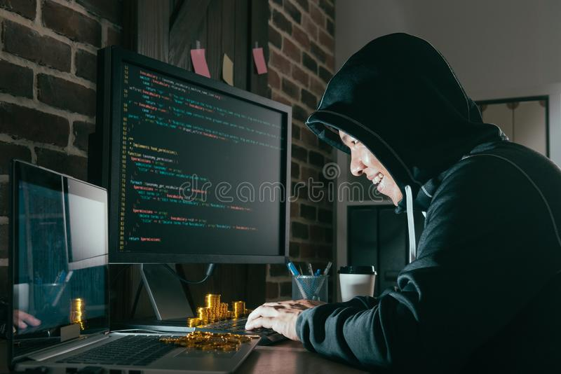 Evil man hacker looking at computer online system stock image