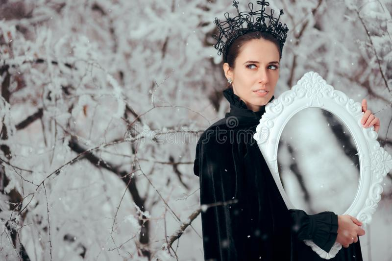 Evil Queen with Magic Mirror in Winter Wonderland royalty free stock images