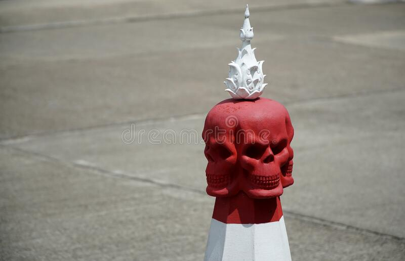 Evil red skull shape road parking cone traffic sign on the public street in front of white temple in Thailand.  royalty free stock images