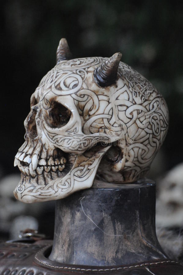 Evil Skull With Horns. This is an evil skull beautifully decorated with drawings all over. The broken nose makes it look even more evil royalty free stock photography