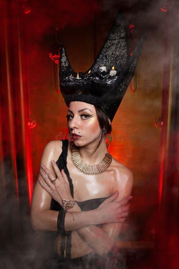 Evil stylish woman witch with big black hat on dark scary smoky background alone stock photo