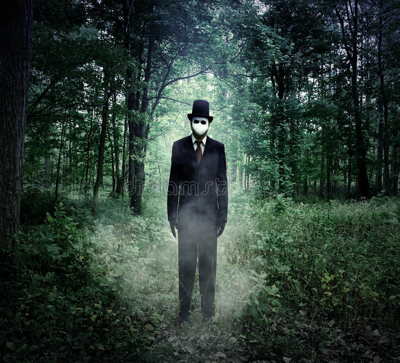 Evil Tall Man Standing in Scary Woods Alone. A scary tall man in a black suit is standing in the dark woods at night with fog for an evil halloween or fear stock photos