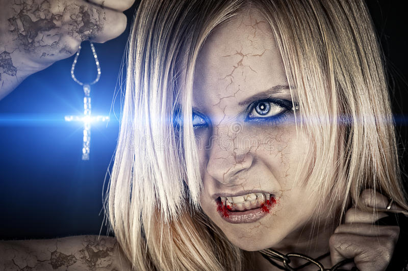 Evil vampire and the bright light. Of the cross royalty free stock photo