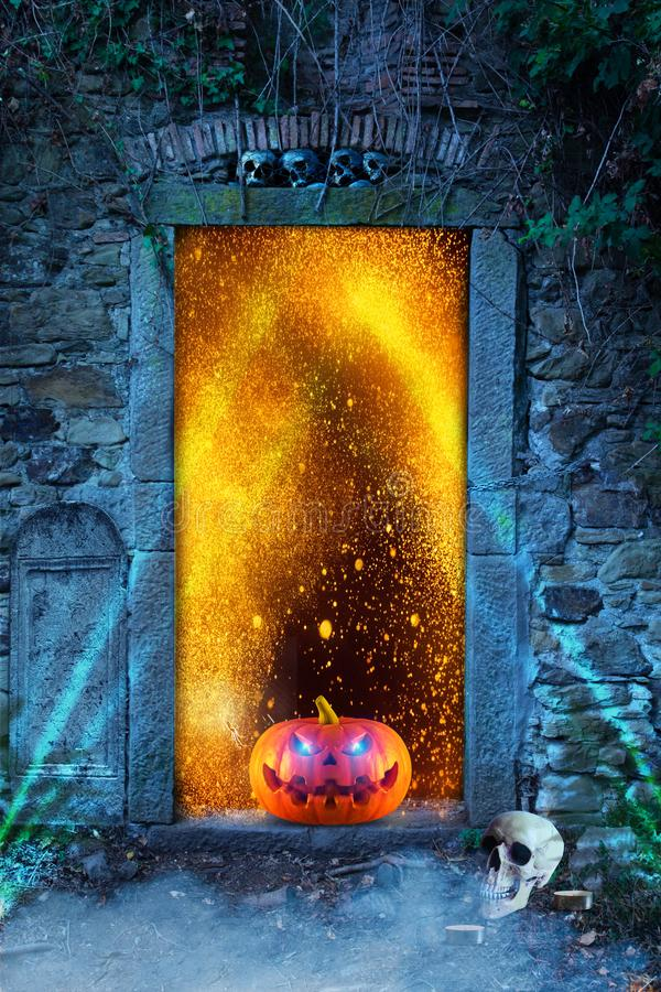 An evilly laughing spooky scary orange pumpkin with glowing eyes in front of a cemetery door with fire sparks at night royalty free stock photography
