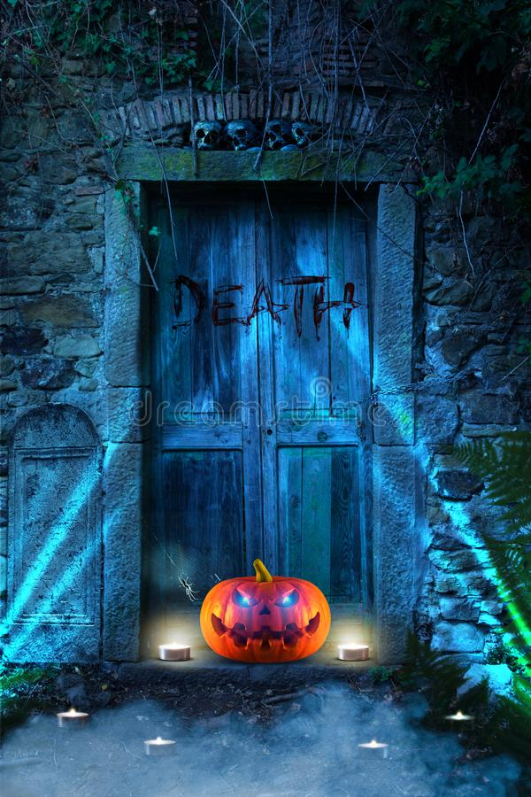 An evilly laughing spooky scary orange pumpkin with glowing eyes in front of a cemetery at night. Copy space royalty free stock photo
