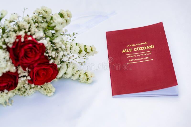 Evlilik cuzdani在白色桌上的结婚证书 免版税库存图片