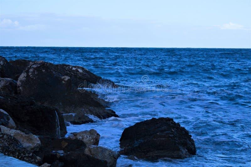 Sea waves crashing on the rocks. Evocative image of sea waves crashing on rocks stock photography