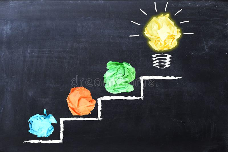 Evoluerend ideeconcept met kleurrijk verfrommeld die document en gloeilamp op stappen op bord worden getrokken stock afbeelding