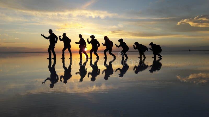 Evolutie van de zonsondergang van de mensenschaduw in Salar De Uyuni, Bolivië stock fotografie