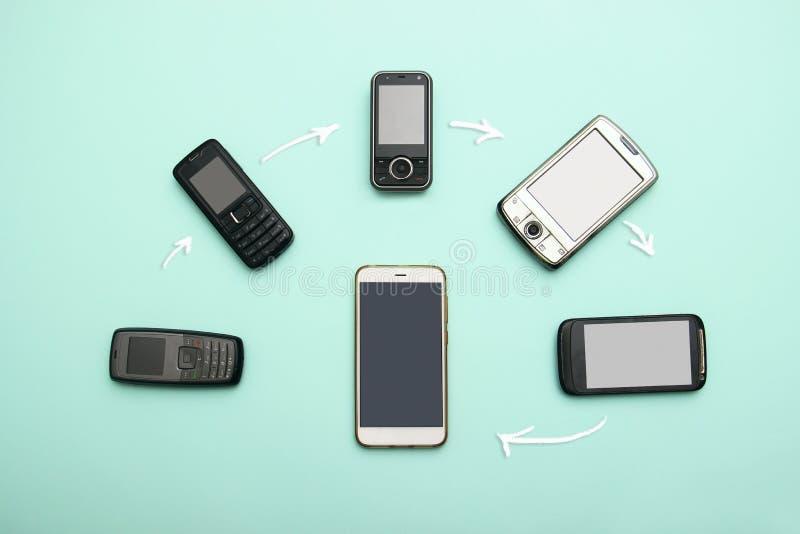 Evoluzione dei telefoni cellulari Concetto del telefono e di pda di sviluppo tecnologico Telefoni d'annata e nuovi Vista superior immagine stock
