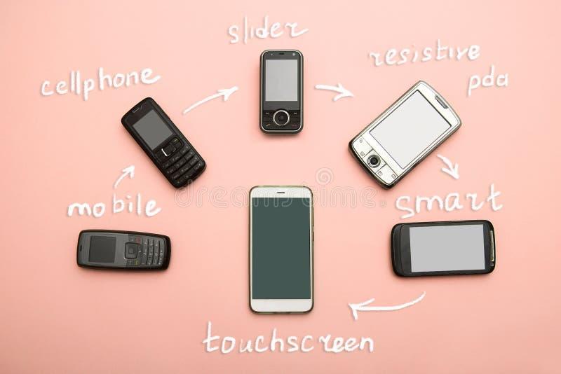 Evoluzione dei telefoni cellulari Concetto del telefono e di pda di sviluppo tecnologico Telefoni d'annata e nuovi Vista superior fotografia stock