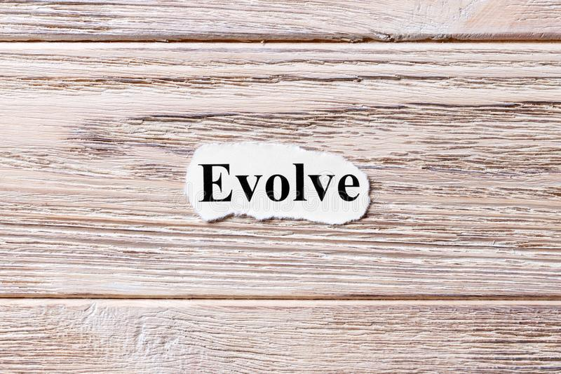 EVOLVE of the word on paper. concept. Words of EVOLVE on a wooden background.  royalty free stock photography