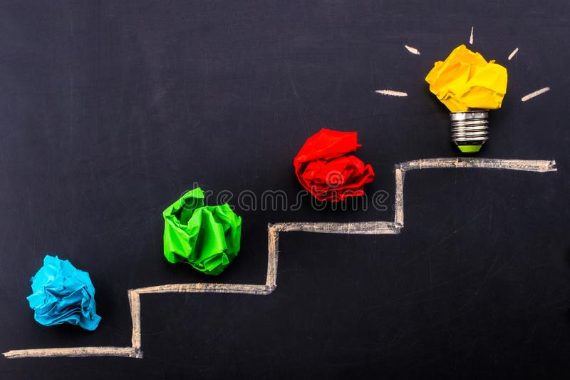 Evolving idea concept with colorful crumpled paper and light bulb on steps drawn on blackboard stock photo