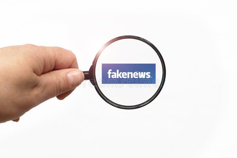 EVPATORIA, ΚΡΙΜΑΙΑ, ΟΥΚΡΑΝΙΑ, ΜΑΡΤΙΟΣ, 12,2018 - που ενισχύουν - γυαλί υπό εξέταση και μια πλαστή λέξη ειδήσεων στο άσπρο υπόβαθρ στοκ εικόνα
