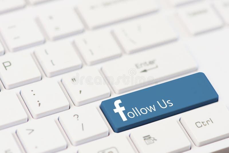 EVPATORIA KRIM, UKRAINA, MARS, 12,2018 - tangenten med text följer oss på det vita bärbar datortangentbordet Facebook stil arkivbilder