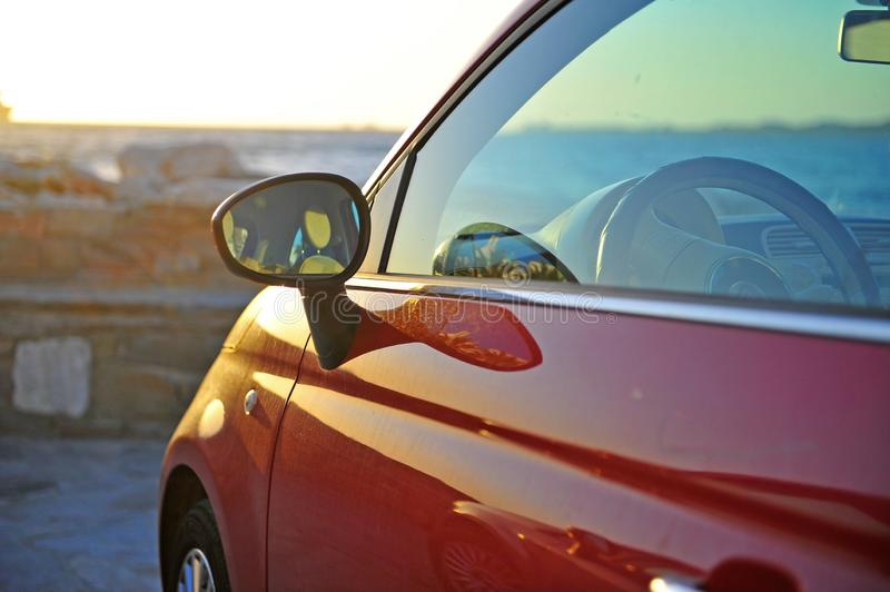 Ew Fiat 500 parked by the sea. Ew red Fiat 500 parked by the sea stock photography