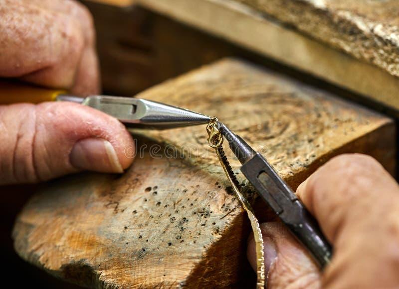 ewelry Produktion Der Prozess der Verbindung eines goldenen Verschlusses mit einem Armband mithilfe zwei Schmuckzangen stockbilder