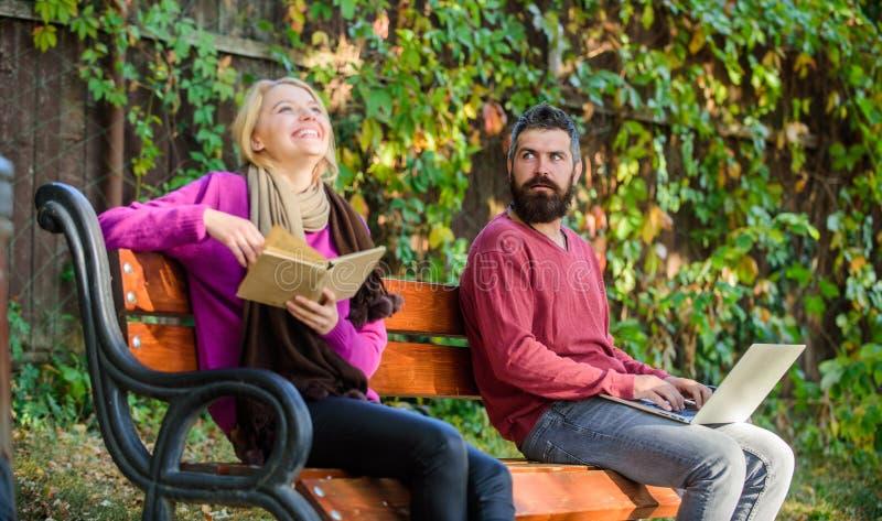 Ewidencyjnego źródła pojęcie Para wydaje czasu wolnego czytanie Para z książki i laptopu rewizi informacją Używa cyfrowego zdjęcie royalty free