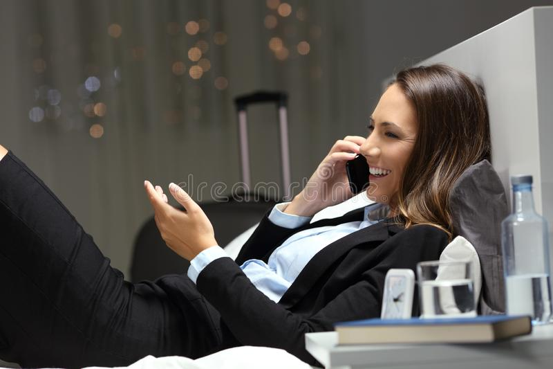 Exécutif ayant la conversation téléphonique d'affaires dans une chambre d'hôtel photos stock