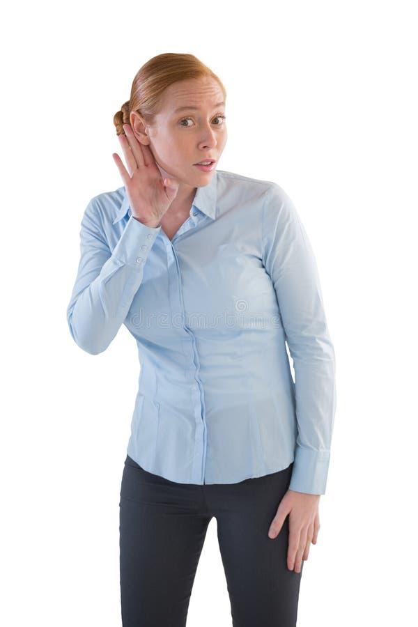 Exécutif féminin écoutant secrètement avec des mains derrière ses oreilles images stock
