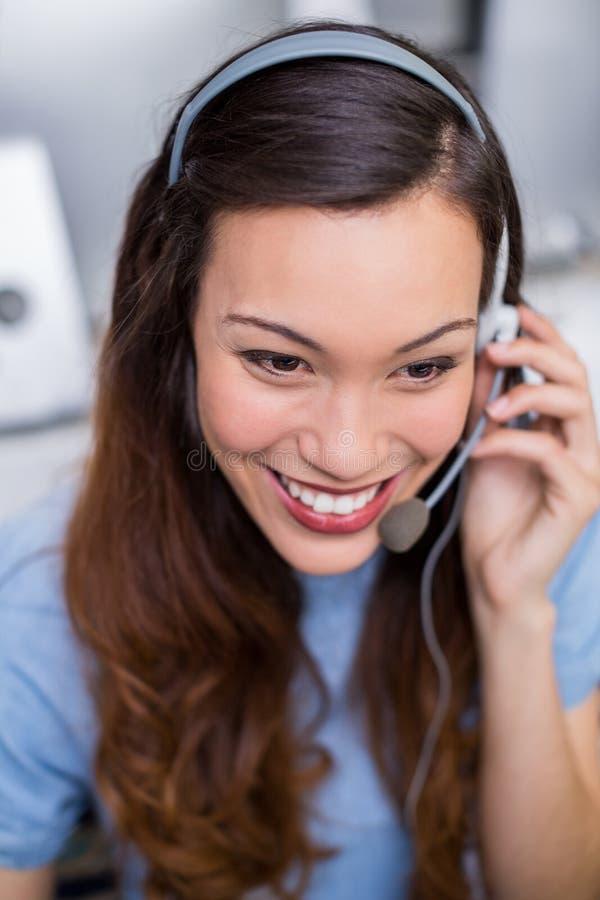 Exécutif féminin de sourire de service client parlant sur le casque au bureau images stock