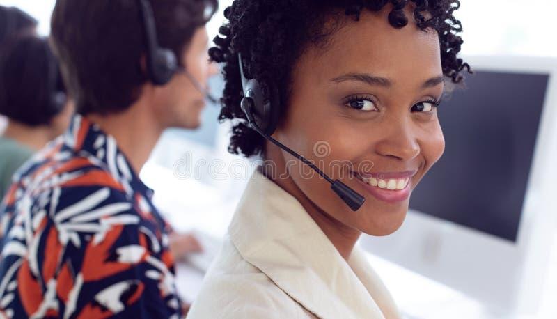 Exécutif femelle de service à la clientèle travaillant sur l'ordinateur au bureau dans le bureau photo libre de droits