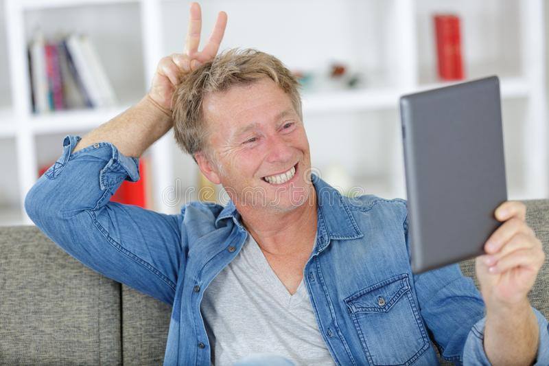 Exécutif heureux de portrait à l'aide du comprimé numérique à la maison photo libre de droits