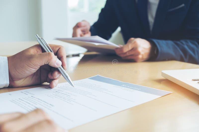 Exécutif lisant un résumé pendant une entrevue d'emploi et un businessma images stock