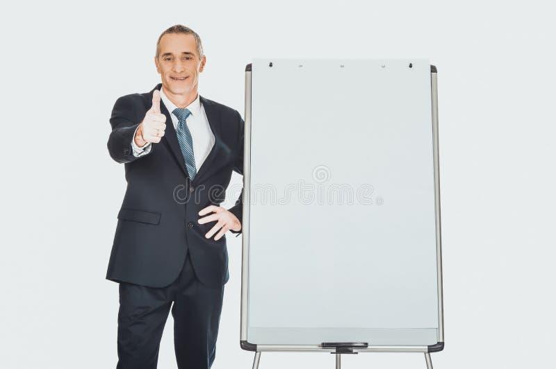 Exécutif masculin avec le signe correct près du tableau de conférence photos libres de droits