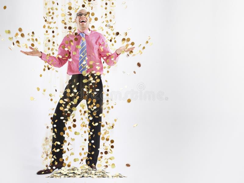 Exécutif masculin heureux sous la douche des pièces d'or photos stock