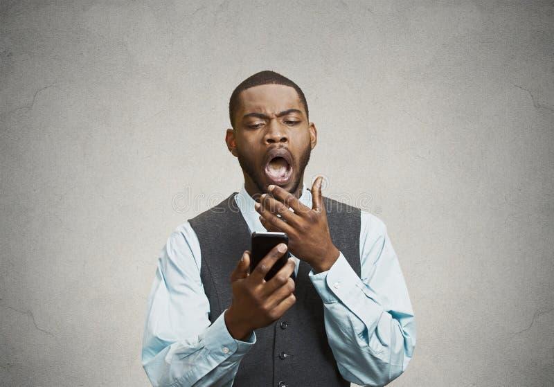 Exécutif tenant le téléphone intelligent, ennuyé par la conversation, textotant image libre de droits