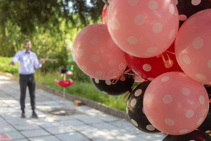 Exécution d'un magicien par une fête d'anniversaire extérieure avec des ballons photographie stock libre de droits