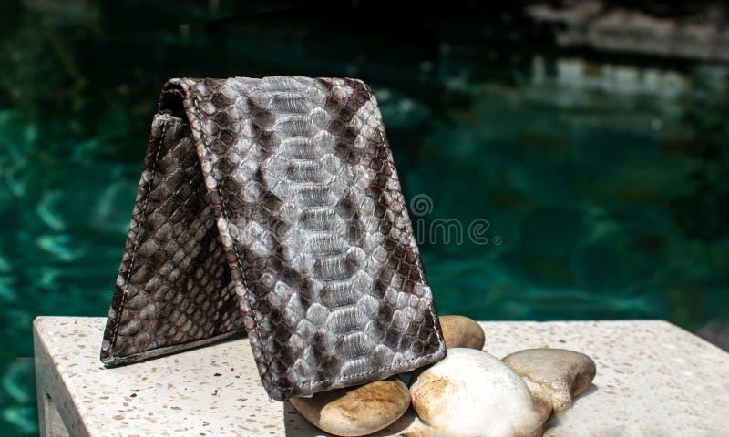 Exótico e luxo da carteira de couro feito à mão, bolsa Multi colorido Ofício de couro Em uma telha de pedra com fundo com Plumeri imagem de stock