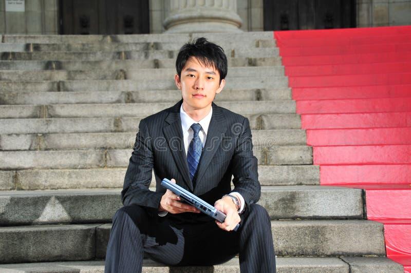 Ex?cutif asiatique intuitif de technologie se reposant avec le carnet images libres de droits