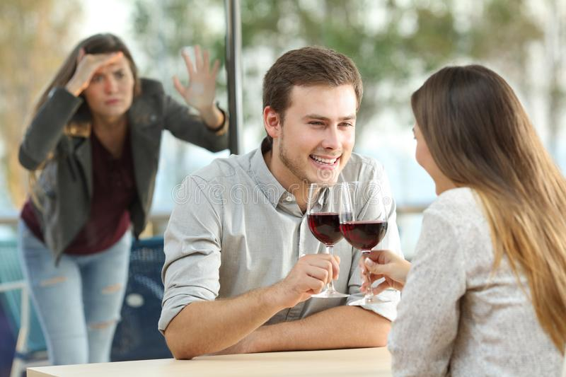 Ex girlfriend spying to a couple in a bar royalty free stock photos