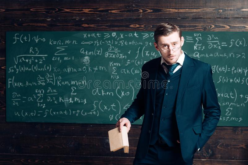 Exacting teacher. Teacher formal wear and glasses looks smart, chalkboard background. Man with high expectations looks royalty free stock images