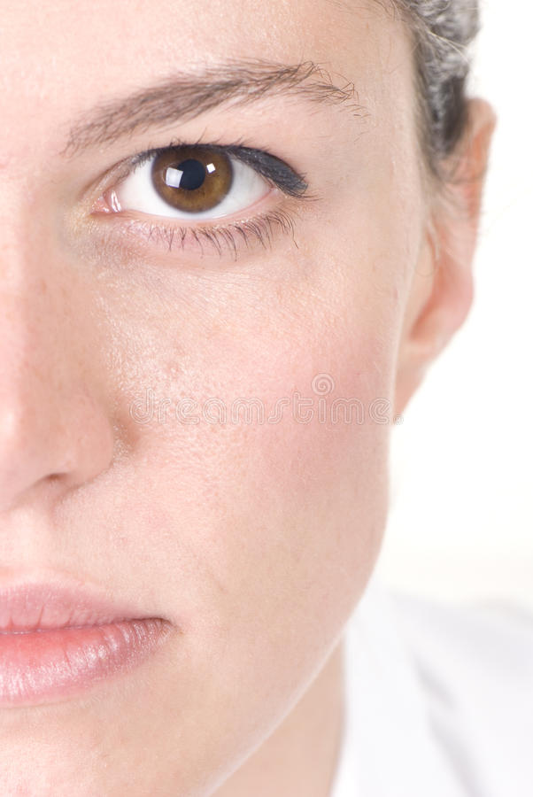 Exactly half of the face. Of a beautiful young woman with brown eyes on white background stock photos