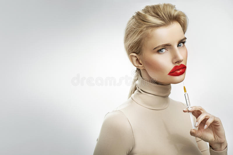 Exaggerated injection to the lips of a beautiful blonde. Exaggerated injection to the lips of a beautiful blond lady royalty free stock images