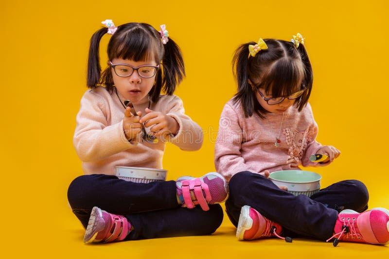 Exakta förtjusande unga flickor med Down Syndrome bärande metallskedar royaltyfri bild
