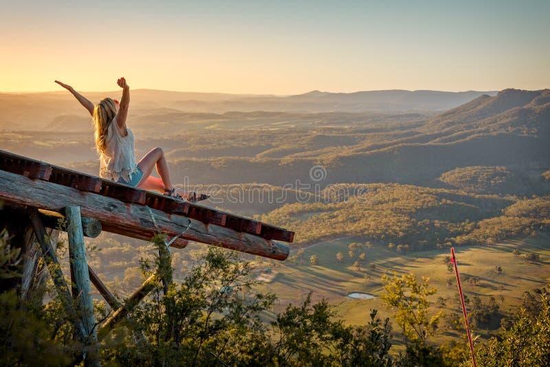 Exaltation se sentante aimante de femme de liberté sur la haute de rampe au-dessus de la vallée photo stock