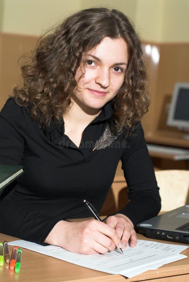 Exam. Female student is passing exam. Primary focus on hands stock photo